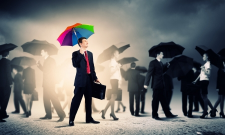 wealth management: Image of pretty businessman with umbrella walking in crowd of people Stock Photo