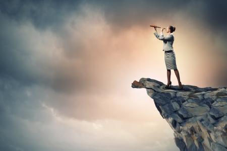 teleskop: Bild der Unternehmerin sucht im Teleskop steht eine Oberseite des Felsens