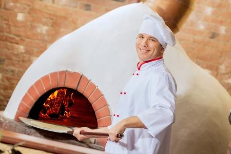 haciendo pan: Imagen de la joven cocinero guapo en la cocina