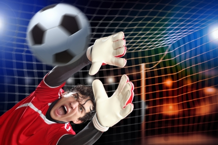 Goalkeeper catches the ball At the stadium, in the spotlight Imagens