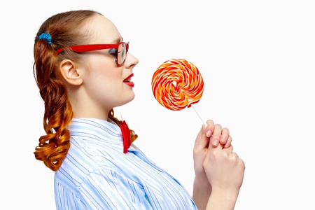 Image of young funny woman in red glasses holding candy photo