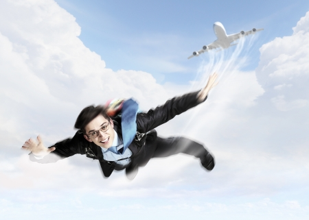 flying man: Conceptual image of young businessman flying with parachute on back Stock Photo