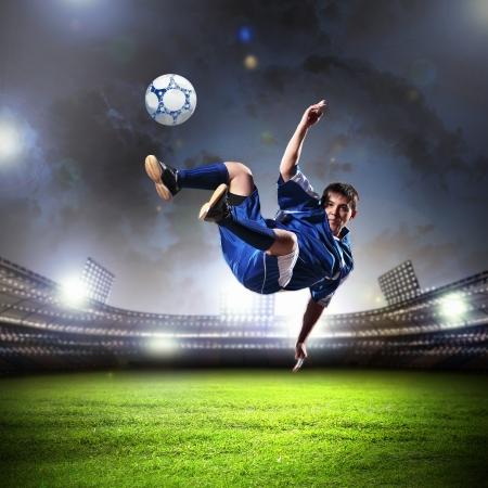 field  soccer: jugador de f?tbol en la camisa azul de golpear la pelota en el aire, en el estadio