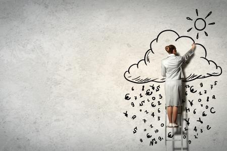 Afbeelding van zakenvrouw staande op de ladder en tekenen op de muur Stockfoto