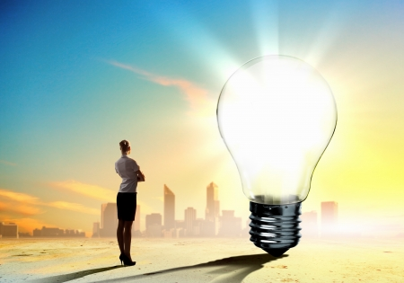 Image of businesswoman looking at light bulb  Green energy concept photo
