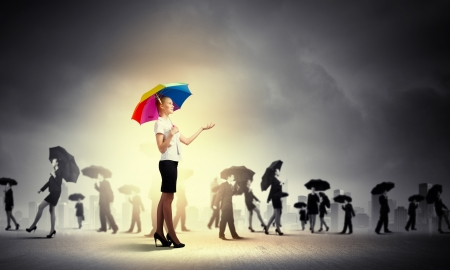 Image of pretty businesswoman with umbrella walking in crowd of people photo