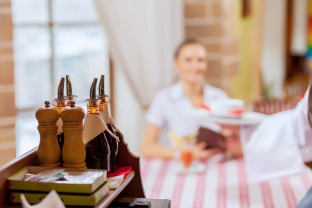 Image of pretty woman sitting at restaurant with menu in hands photo