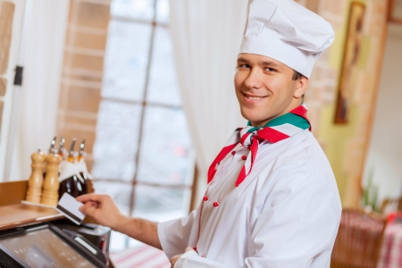 Image of handsome chef inserting card in terminal photo