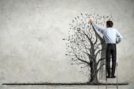 economie: Achteraanzicht beeld van zakenman tekening graphics op muur