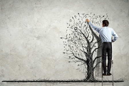 investment strategy: Back view image of businessman drawing graphics on wall