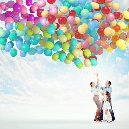 friends and family: Image of happy family holding bunch of colorful balloons Stock Photo