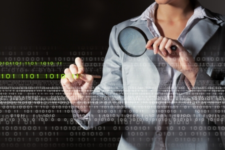 infect: Businesswoman with magnifier glass examining binary code