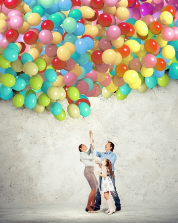 Image of happy family holding bunch of colorful balloons photo