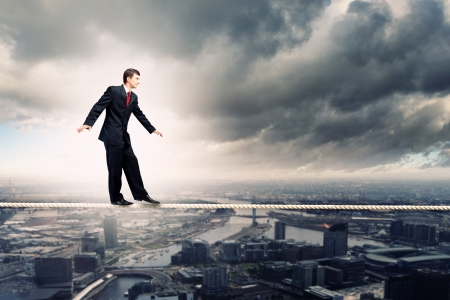 Image of pretty businessman balancing on rope photo