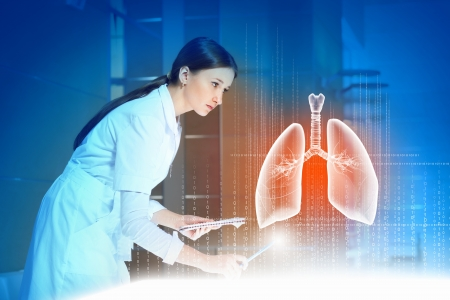 Image of pretty woman therapist examining virtual image of lungs photo