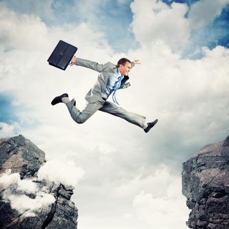 brincando: Imagen de joven empresario saltando sobre brecha