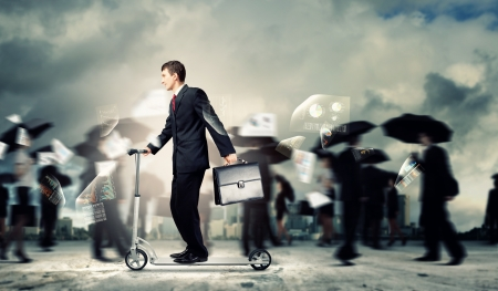 Image of young businessman in black suit riding scooter Stock Photo - 20327198