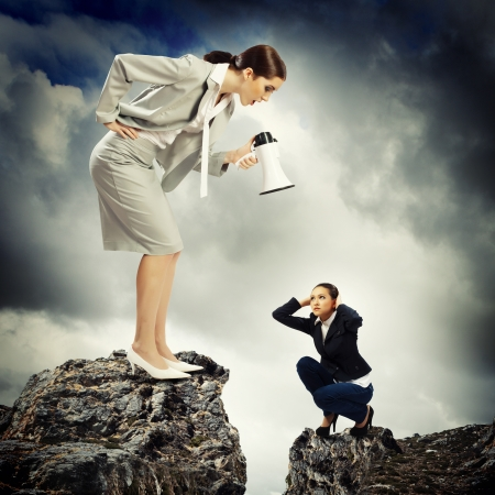 anger: Angry businesswoman with megaphone shouting at colleague