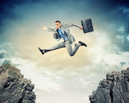 impediment: Image of young businessman jumping over gap Stock Photo