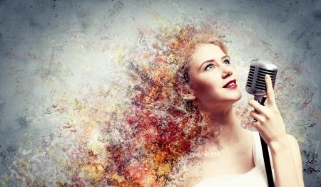 karaoke singer: Image of female blonde singer holding microphone against color background