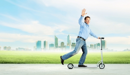 Image of young businessman in black suit riding scooter Stock Photo - 20327172