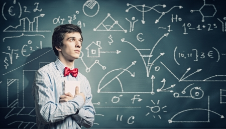 Image of thoughtful male student holding notebook in classroom Stock Photo - 20327301