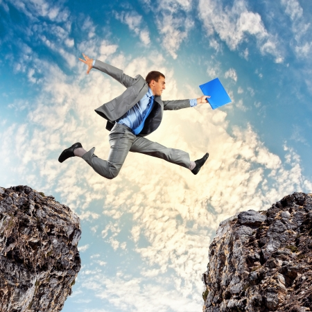 aspiration: Image of young businessman jumping over gap Stock Photo