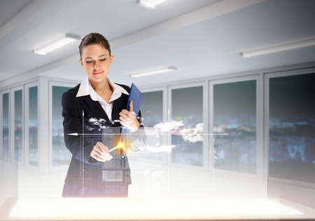 Image of young businesswoman clicking icon on high-tech picture photo