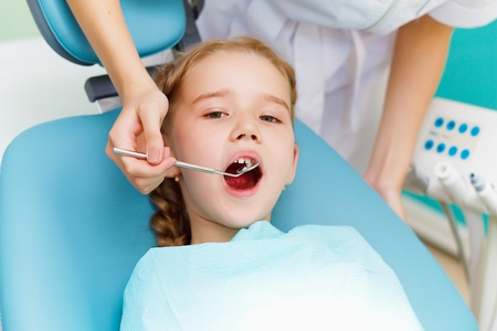 oral care: Little girl sitting in the dentists office