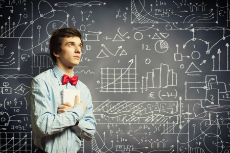 schooling: Image of thoughtful male student holding notebook in classroom