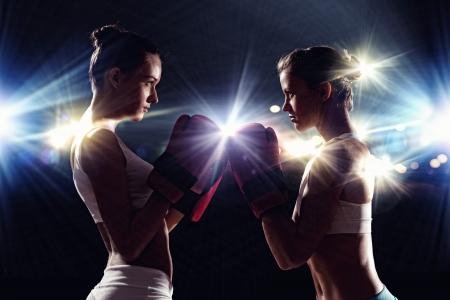 mujeres peleando: Dos mujeres del boxeador en guantes saludan antes de lucha