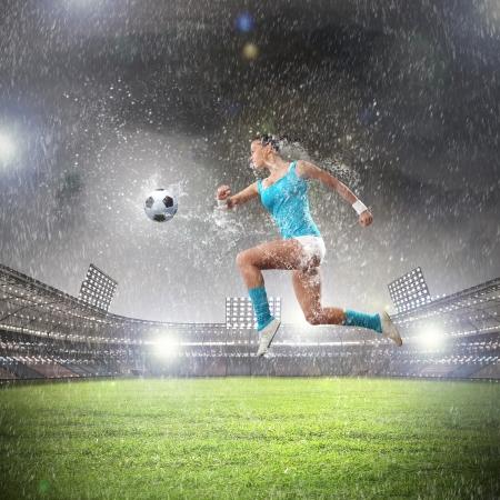 젊은 여성 축구 선수가 공을 치는 이미지 스톡 콘텐츠