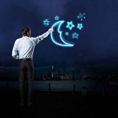 Businessman draws a glowing signs in the dark sky photo