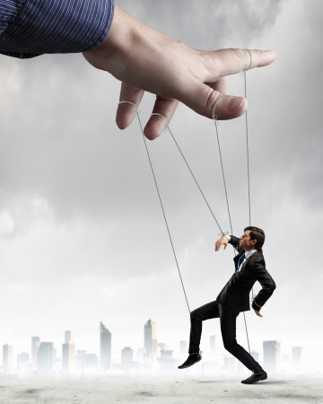 manipulate: Businessman marionette on ropes controlled by puppeteer against city background