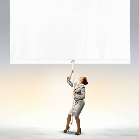 Image of businesswoman pulling blank banner  Place for text photo