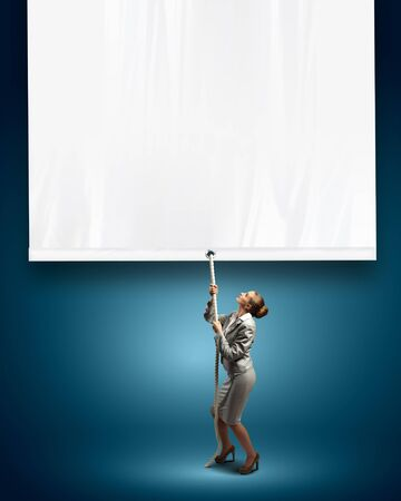 Image of young businesswoman pulling blank banner  Place for text photo