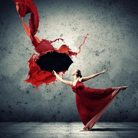 ballet dancing: ballet dancer in flying satin dress with umbrella under the paint