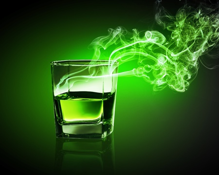 Glass of green absinth with fume going out photo