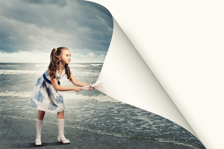 turn: Little girl turning page with another reality Stock Photo