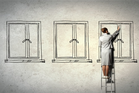 Image of businesswoman standing on ladder and drawing on wall photo