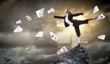 printed material: young businesswoman standing on one leg atop of mountain against diagram background