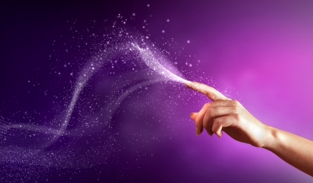 entertainment event: magical hand conceptual image with sparkles on colour background