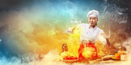 Asian female Kochen mit Magie gegen farbigen Hintergrund Standard-Bild - 20661924