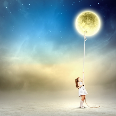 power nap: Image of little girl in white dress pulling moon Stock Photo