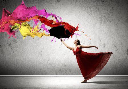 rain umbrella: ballet dancer in flying satin dress with umbrella under the paint