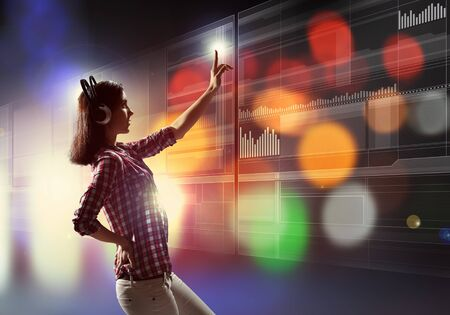 digital music: Image of young woman with headphones touching virtual screen Stock Photo