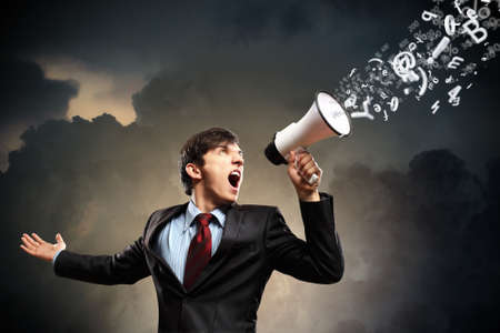 young businessman in black suit screaming into megaphone photo