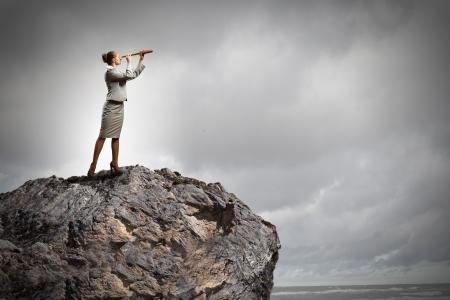 회사: 사업가의 이미지 바위의 꼭대기에 서있는 망원경을보고