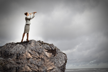 Image of businesswoman looking in telescope standing atop of rock Stock Photo