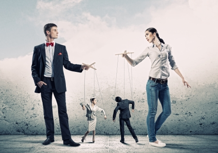 dictator: Image of man and woman with marionette puppets Stock Photo